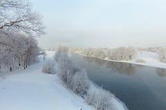 банкы покрыли снежок реки в декабре Стоковые Изображения