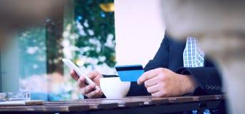 Банк интернета, онлайн торгуя концепция Подрезанный взгляд рук бизнесмена держа мобильный телефон и промежуток времени кредитной  стоковая фотография rf
