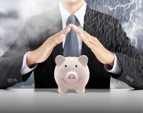Банк пинка крышки руки бизнесмена piggy керамический с предпосылкой шторма проливного дождя стоковые изображения