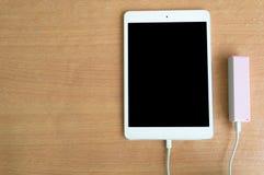 Банк силы кабеля USB с таблеткой на деревянной таблице Стоковое фото RF
