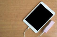 Банк силы кабеля USB с таблеткой на деревянном столе Стоковые Изображения
