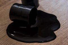 2 барабанчика топлива с разлитым маслом на столе Стоковое Изображение