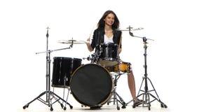 Барабанщик девушка начинает сыграть напористую музыку, она усмехается Белая предпосылка сток-видео