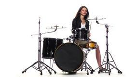 Барабанщик девушка начинает сыграть напористую музыку, она усмехается Белая предпосылка движение медленное сток-видео