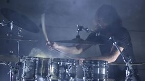 Барабанщик играет барабанчики в ангаре движение медленное