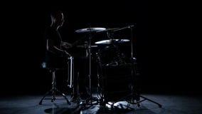 Барабанщик играет напористую музыку на барабанчике Черная предпосылка Взгляд со стороны акции видеоматериалы
