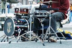 Барабанщик играя барабанчики на blured предпосылке города Человек играя барабанчики на улице Музыкант улицы выполняя с барабанчик стоковые изображения