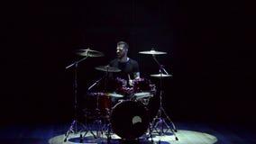 Барабанщик играя на барабанчике установил на черную предпосылку сток-видео