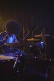 Барабанщик при frizzy волосы играя набор барабанчика в ночном клубе Стоковая Фотография