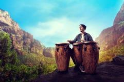 Барабанщик с деревянными барабанчиками играет в долине пустыни стоковое изображение
