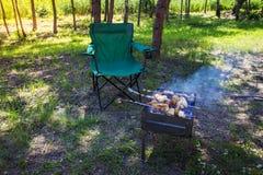 Барбекю в природе Остатки дальше под открытым небом Барбекю с мясом зажарило в духовке на огне или углях стул лагеря около барбек Стоковое фото RF