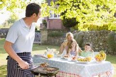 барбекю наслаждаясь семьей Стоковое Фото