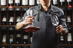 Бармен в рисберме держит сосуд с красным вином и стеклом Стоковое Изображение