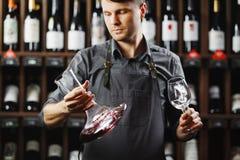 Бармен в рисберме держит сосуд с красным вином и стеклом Стоковые Фото