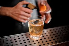 Бармен готовый для того чтобы увольнять оранжевый пыл и добавлять его к свежему алкогольному напитку стоковая фотография