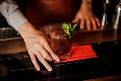 Бармен держит коктеиль с мятой в его руке Отсутствие стороны Стоковая Фотография RF