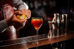 Бармен добавляет пыл лимона к коктеилю на счетчике бара Селективный фокус стоковая фотография rf