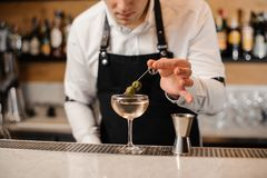 Бармен добавляя 2 зеленых оливки в стекло с питьем Стоковое фото RF