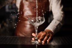 Бармен лить в стекло шампанского и делая выплеск Стоковые Фотографии RF
