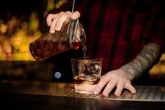 Бармен лить свежий сильный коктейль вискиа в стекло стоковая фотография rf