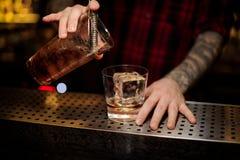 Бармен лить свежий сильный коктейль вискиа в стекло стоковое фото