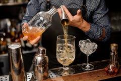 Бармен лить часть сиропа от бутылки в большое стекло коктеиля Стоковые Изображения RF