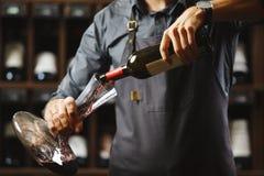 Бармен льет красное вино в прозрачном сосуде в погребе Стоковая Фотография RF