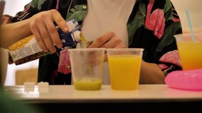 Бармен льет сок от стога металла в пластиковые чашки Конец-вверх рук бармена Счетчик Адвокатуры акции видеоматериалы