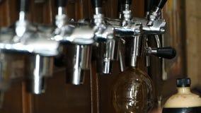 Бармен льет темное пиво в пластиковой бутылке Закрывает крышку бутылки и кладет в белую сумку сток-видео