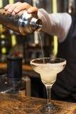 Бармен на работе, подготавливая коктеили Лить маргарита к стеклу коктеиля Стоковое Изображение