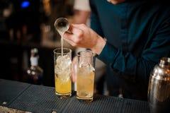 Бармен подготавливает 2 спиртных коктеиля, добавляя апельсиновый сок стоковое изображение rf