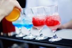 Бармен подготавливая коктеиль с голубым и красным сиропом Стоковое Фото