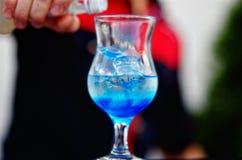 Бармен подготавливая коктеиль с голубым сиропом Стоковые Фото