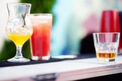 Бармен подготавливая коктеиль с желтым и красным сиропом Стоковое Фото