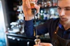 Бармен при шейкер подготавливая коктеиль на баре Стоковое фото RF