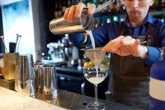 Бармен при шейкер подготавливая коктеиль на баре Стоковые Фото