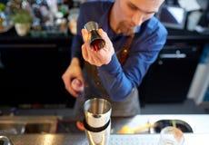 Бармен при шейкер подготавливая коктеиль на баре Стоковая Фотография