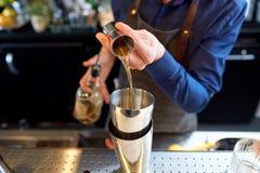 Бармен при шейкер подготавливая коктеиль на баре Стоковые Фотографии RF