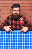 Бармен рекомендует попробовать напиток Бармен с бородой на строгой стороне указывая вниз с указательным пальцем Человек в checker Стоковое Изображение