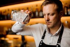 Бармен смешивая спиртной коктеиль с льдом используя стрейнер и стекло стоковое изображение