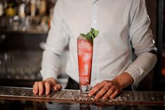 Бармен с стеклом вкусного свежего и сладостного коктеиля лета mojito клубники Стоковое фото RF