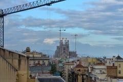 БАРСЕЛОНА, ИСПАНИЯ - 28-ОЕ АПРЕЛЯ: Взгляд Sagrada Familia от террасы на крыше Касы Mila Gaudi или Ла Pedrera 28-ого апреля 2016 Стоковая Фотография