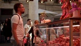 Барселона, Испания - сентябрь 2018: Старый открытый рынок Boqueria Человек осматривает витрину с jamons акции видеоматериалы