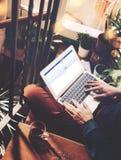 Барселона, Испания -01 02 2016: Человек подписывает вверх страницу facebook Родовая компьтер-книжка дизайна на его коленях вертик Стоковое фото RF