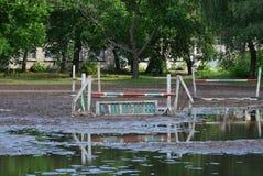 барьер стоит в грязи и лужице на тренировочном поле ипподрома стоковые изображения