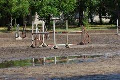 Барьер стоит в грязи и лужице на тренировочном поле ипподрома стоковое изображение