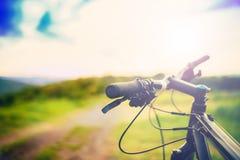 Бар ручки велосипеда на заходе солнца на горной тропе детали деятельностей при спорта Стоковая Фотография