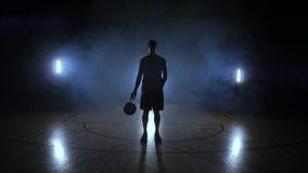 Баскетболист идет к камере и стучает шариком на том основании после этого останавливает и держит шарик смотря видеоматериал