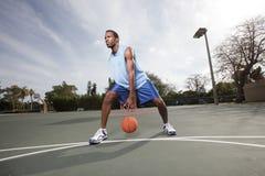 Баскетболист капая шарик Стоковые Изображения