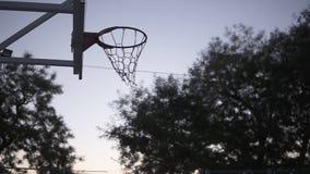 Баскетболист молодой женщины тренируя outdoors на баскетбольной площадке Сумрак утра акции видеоматериалы